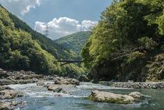 Hozugawa River by the rocky green hills. Hozugawa River along the rocky green hills. A view with train bridge and power lines. Arashiyama, Kyoto. Japan Royalty Free Stock Photography