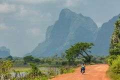 Local burmese people riding motorbike on the country road near Hpa-an, Myanmar Stock Photos
