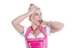 Häpen blond kvinna i dirndlen - som isoleras på vit Arkivfoto