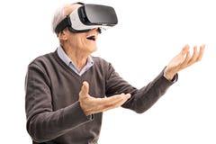 Häpen pensionär som använder en VR-hörlurar med mikrofon Royaltyfri Fotografi