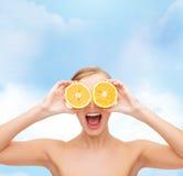 Häpen ung kvinna med orange skivor Royaltyfria Bilder