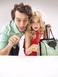 Häpna par som stirrar på försäljningar Fotografering för Bildbyråer