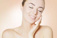 Hppy skincare :应用奶油的妇女于面孔 免版税库存照片