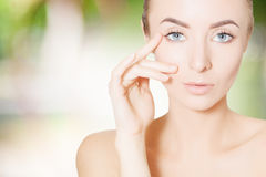 Hppy skincare: woman applying creme to face Stock Photography