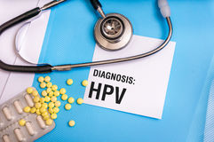 HPV word written on medical blue folder with patient files. Pills and stethoscope on background Royalty Free Stock Photos