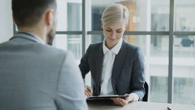 HR businesswoman having job interview with young man in suit and watching his resume application in modern office. Indoors