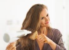 Hår för kvinnaborsta och slaguttorkning i badrum Arkivfoton