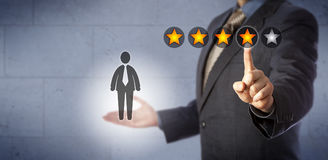 HR Manager Giving A Four Star Rating Out Of Five. Blue chip human resources manager is giving a male employee a four star rating out of five. Business concept royalty free stock photo