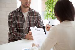 Hr manager holding reading smiling applicants resume at job inte. Hr manager reading smiling applicants resume at job interview, recruiter employer holding cv of royalty free stock image