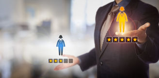 HR Manager Rating Two Female Employee Icons. Unrecognizable manager is evaluating a female employee icon with a five star rating versus one with three. HR royalty free stock photo