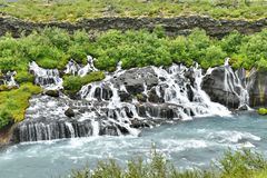 Hraunfossar lavavattenfall i västra Island arkivbilder