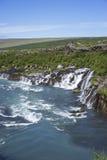 Hraunfossar-Wasserfall, der von unterhalb Hallmundarhraun-Lava f auftaucht Lizenzfreie Stockfotografie