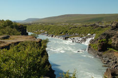 Hraunfossar waterfalls. In Iceland and tourists watching it from a plateau Stock Photo