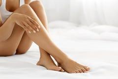 Hårborttagning Slutet upp kvinna räcker rörande långa ben, mjuk hud Fotografering för Bildbyråer