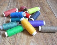 hreads dei colori luminosi differenti su fondo di legno immagine stock
