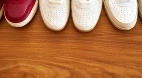 Hree对木表面上的红色和白色运动鞋鞋子 库存照片