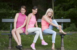 Hree young female friends seated on a bench, outdoors Stock Images