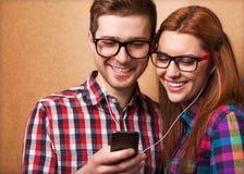 Hörende Musik der jungen Paare Stockbild