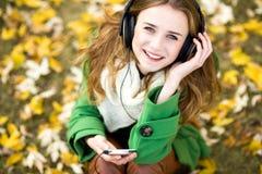 Hörende Musik des Mädchens draußen Stockfotos