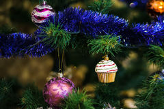 Сhristmas ball in shape of muffin on Christmas tree. Stock Photos