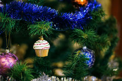 Сhristmas ball in shape of muffin on Christmas tree. Stock Images