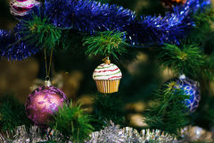 Сhristmas ball in shape of muffin on Christmas tree. Royalty Free Stock Photos