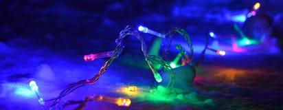 сhristmas lights garland on the snow at night Royalty Free Stock Photos