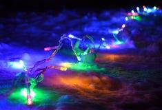 сhristmas lights garland on the snow at night Stock Photos