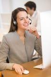 Härlig affärskvinna i kontoret på telefonen, hörlurar med mikrofon Fotografering för Bildbyråer