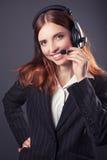 Härlig affärskvinna med hörlurar mot mörk grå backg Royaltyfri Fotografi