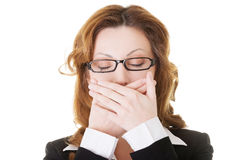 Härlig affärskvinna med stängda ögon som täcker hennes mun. Fotografering för Bildbyråer