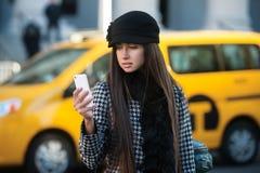 Härlig affärskvinna som kallar taxien genom att använda mobiltelefonen i stadsgatan Arkivfoton