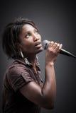 Härlig afrikansk kvinna som sjunger med mikrofonen Arkivbilder