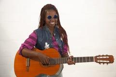 Härlig afrikansk kvinna som spelar gitarren Arkivfoton