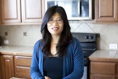 Härlig asiatisk kvinna i tidiga forties som står i kök Fotografering för Bildbyråer