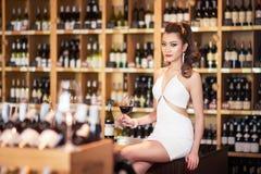 Härlig asiatisk kvinna med ett exponeringsglas av vin Arkivbilder