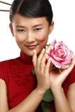 Härlig asiatisk kvinnastående med rosa färgblomman Arkivfoto