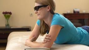 Härlig attraktiv ung kvinna i den blåa t-skjortan som ligger på soffan och hållande ögonen på TV i 3D-glasses arkivfilmer