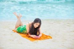 Härlig biracial tonårig flicka som ligger på den tropiska stranden med telefonen Arkivbilder