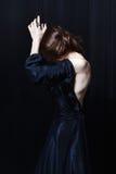 Härlig blek tunn kvinna i en tung svart siden- taftklänning Arkivfoto