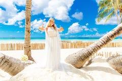 Härlig blond brud i den vita bröllopsklänningen med stor lång vit Royaltyfri Foto