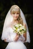 Härlig blond brud med bröllopbouqet i händerna Arkivbilder