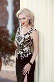 Härlig blond dam i elegant klänning frisyr Röd kantmakeup Arkivfoto