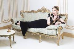 Härlig blond kunglig kvinna som lägger på en retro soffa i ursnygg lyxig klänning Royaltyfria Bilder
