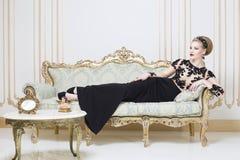 Härlig blond kunglig kvinna som lägger på en retro soffa i ursnygg lyxig klänning Fotografering för Bildbyråer