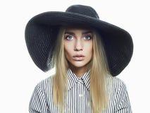 Härlig blond kvinna i svart hatt Arkivbild