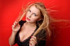 Härlig blond kvinna i svart klänning med på glänt bröstet Arkivfoton