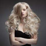 Härlig blond kvinna. Lockigt långt hår Arkivbild