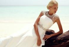 Härlig brud i den eleganta bröllopsklänningen som poserar på den tropiska stranden Royaltyfri Bild