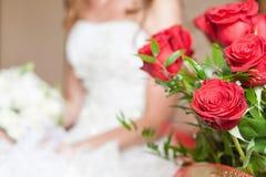 Härlig brud och röd rosbukett Arkivbild